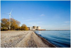 A wind turbine stands on the shore near the nuclear power plant in Pickering, Ont.