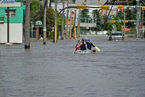 People paddle down the streets of Calgary flowing a flood in June 2013.