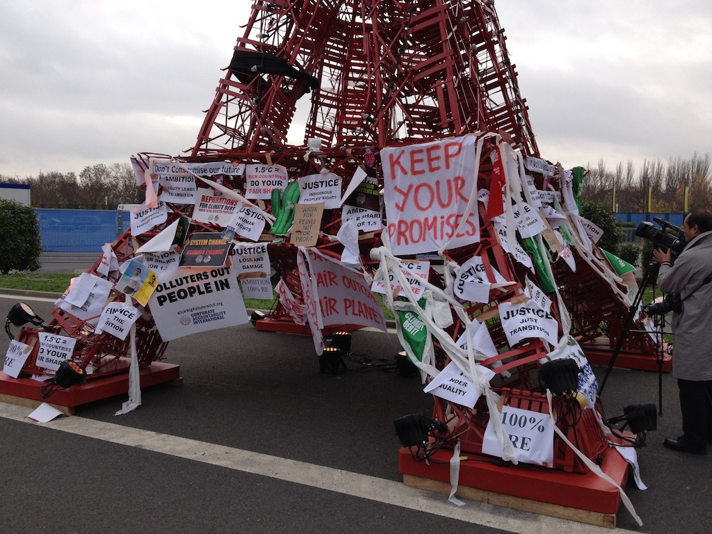 Protest signs adorn a mini Eiffel Tower at COP21. Photo: Josha MacNab.